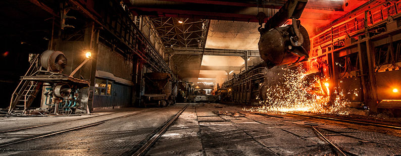 Steel mill with large ladel and sparks